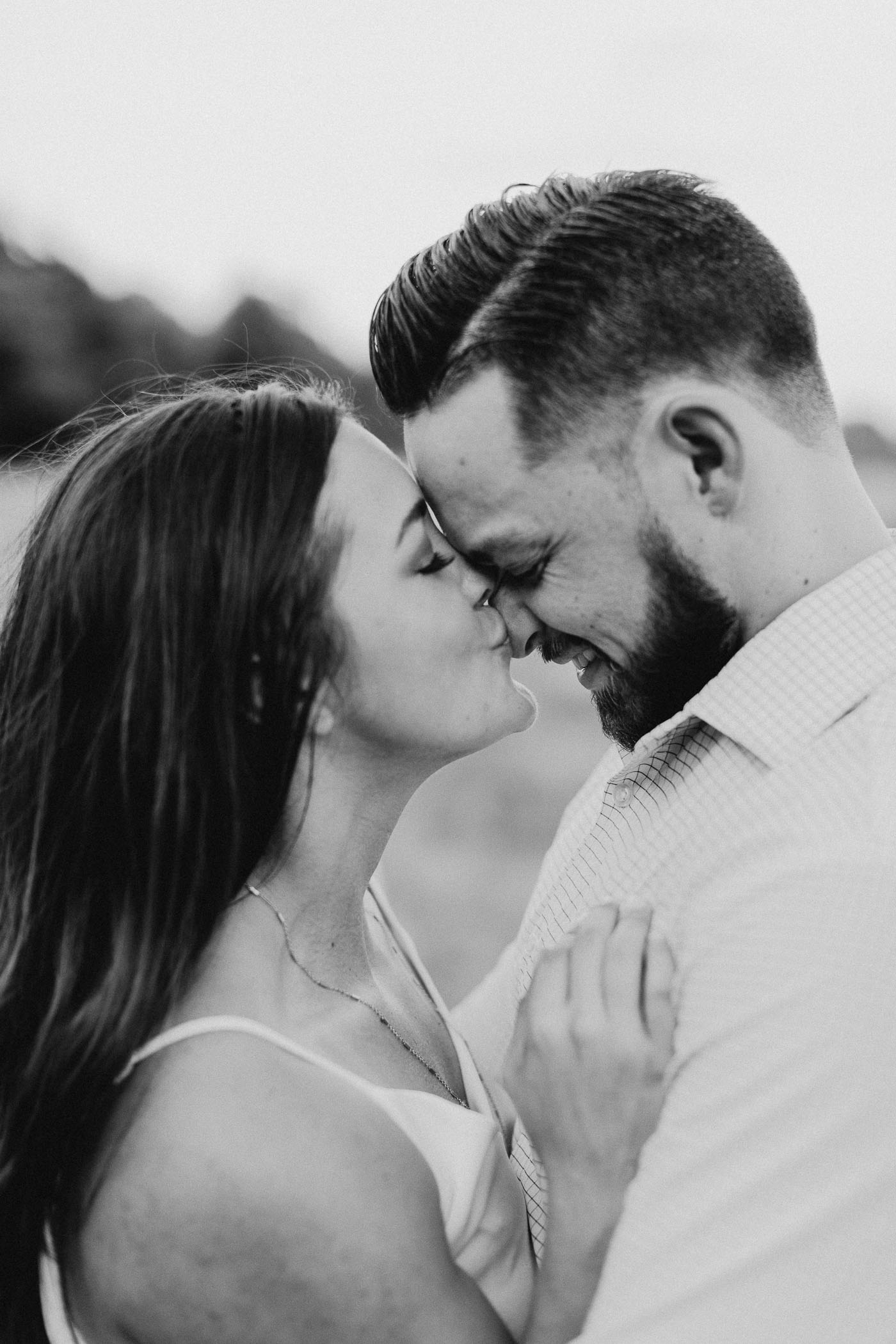 black and white of girl kissing finances face during engagement session