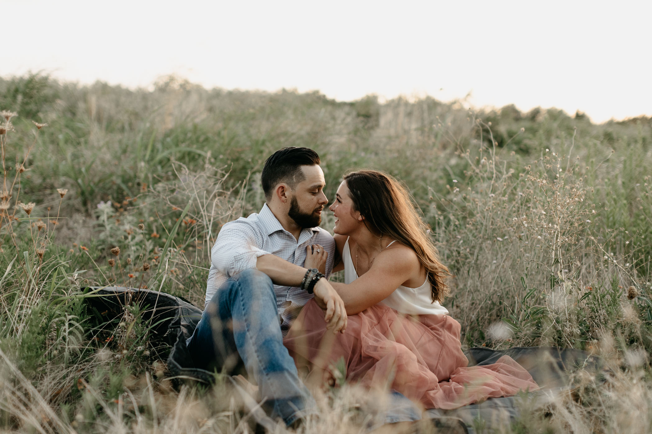 couple being romantic while sitting in tall grass in DFW