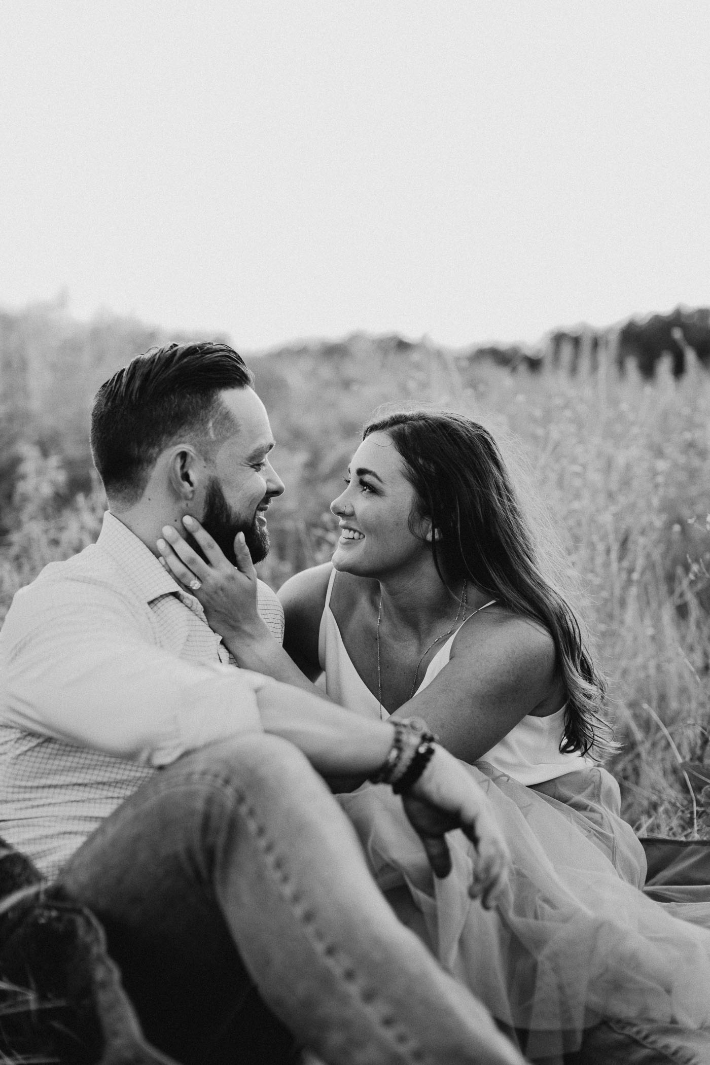 black and white of couple looking at each other while sitting in a field