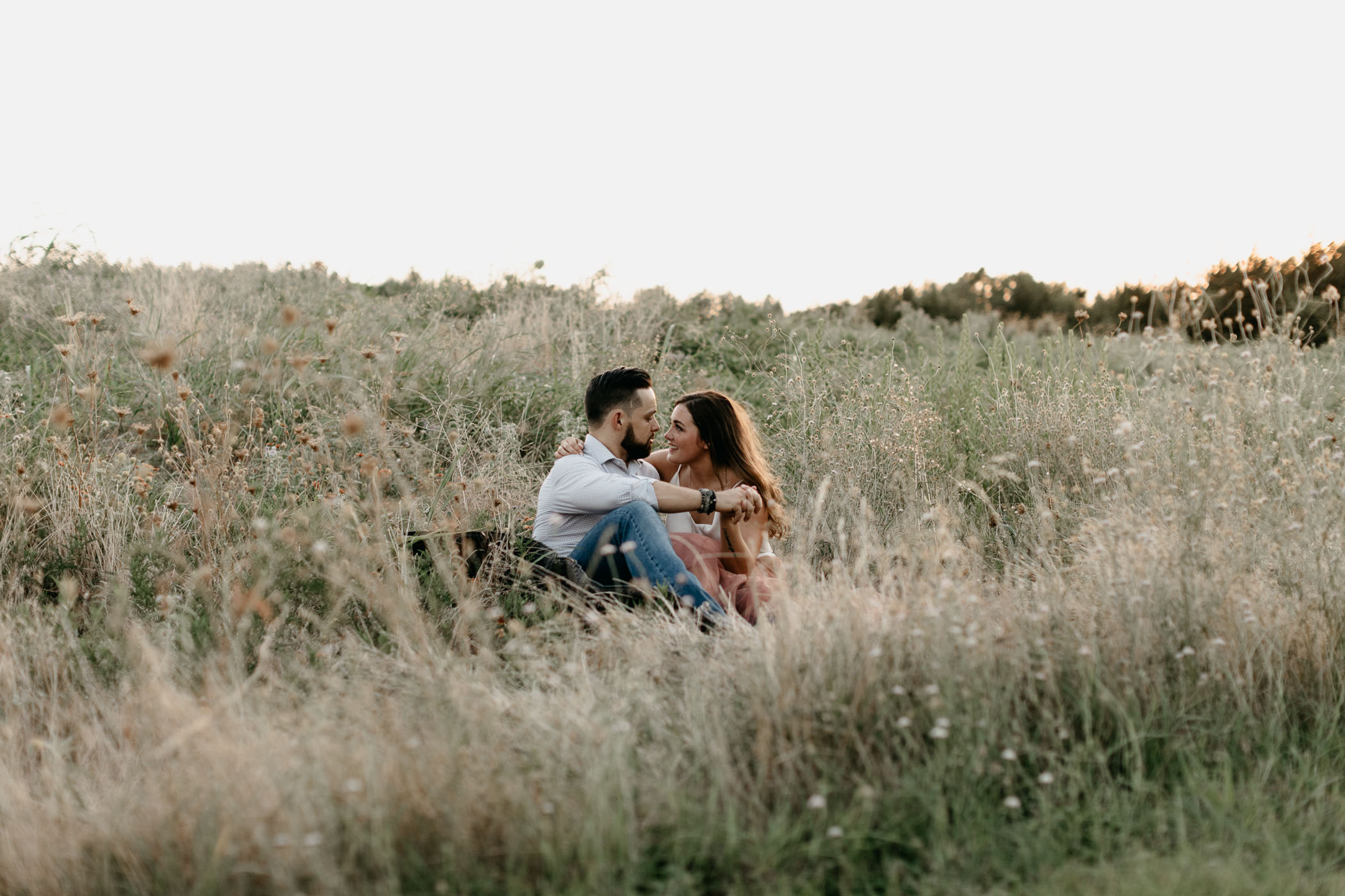 engaged couple sitting in grass during engagement session in DFW