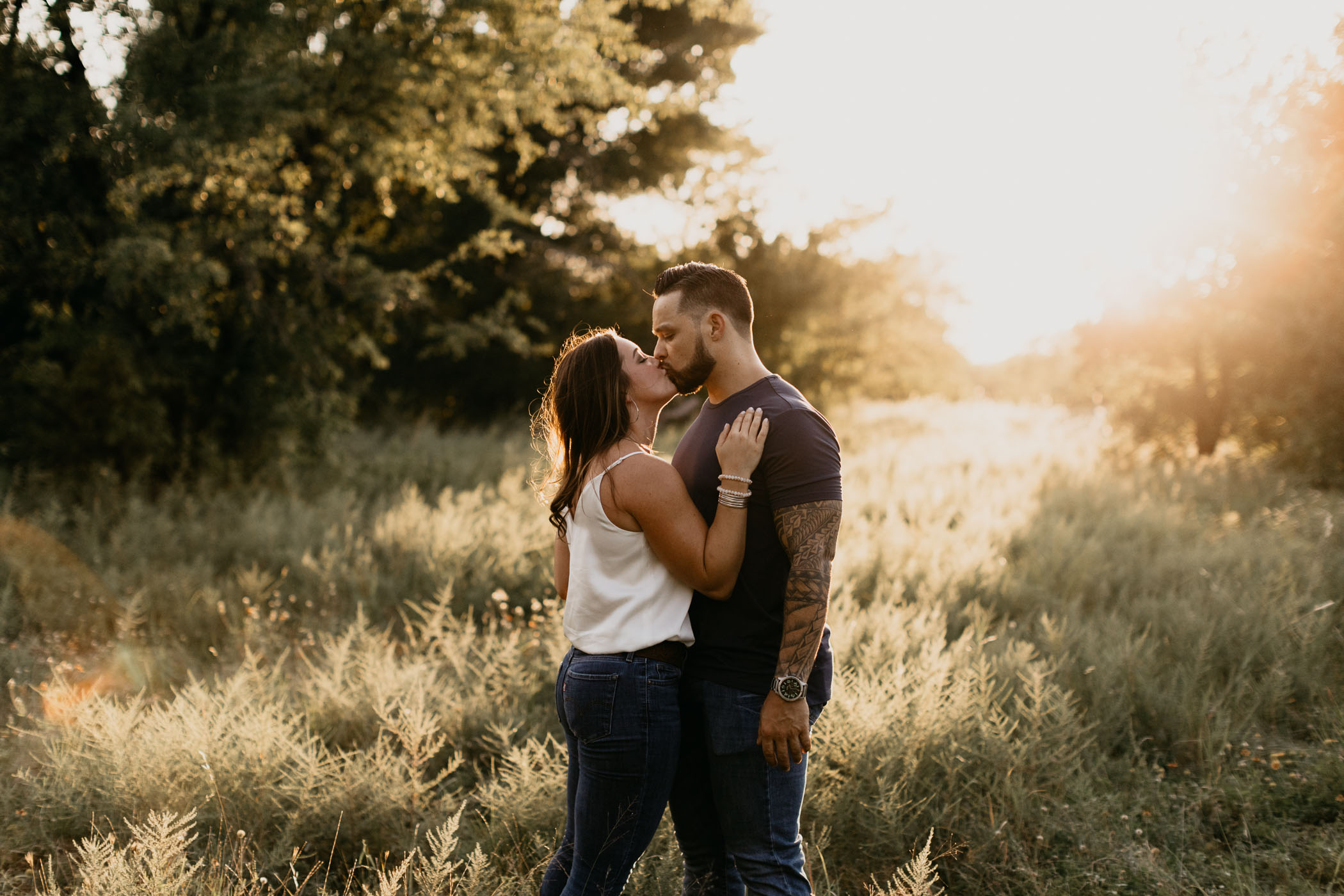 couple kissing at sunset during summer engagement session at Arbor Hills in Plano
