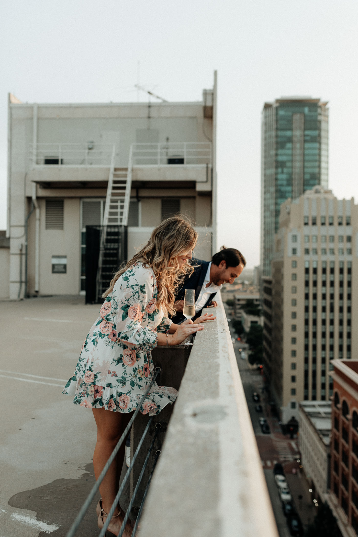 Couple looking over side of parking garage during fun engagement session in DFW