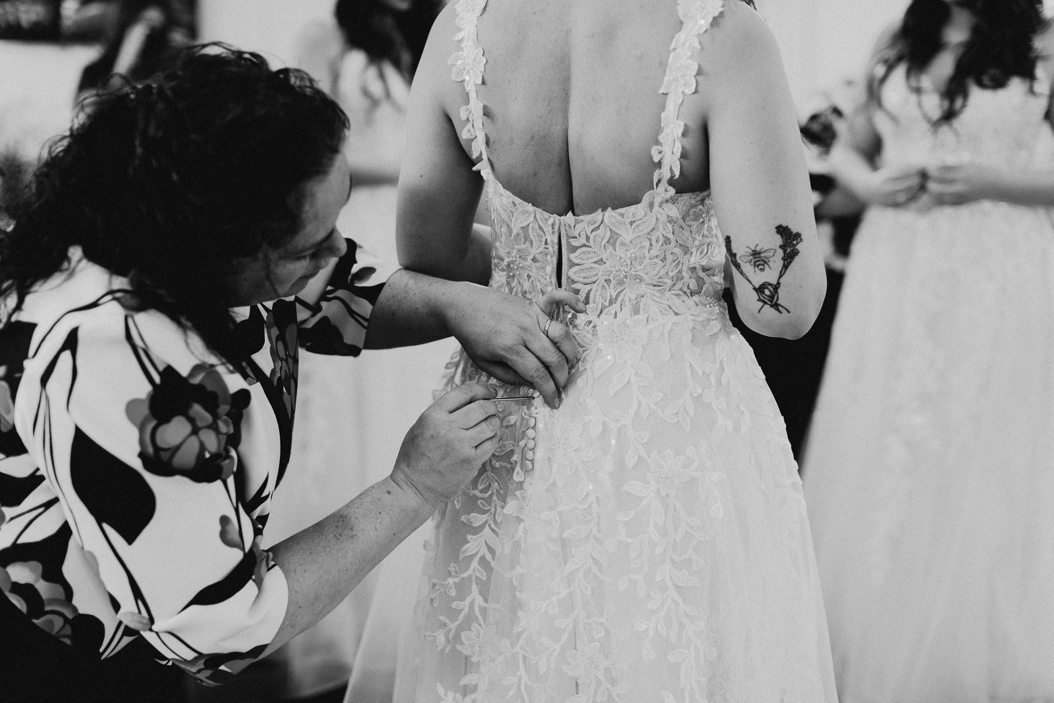 Black and white of bride putting on her wedding dress