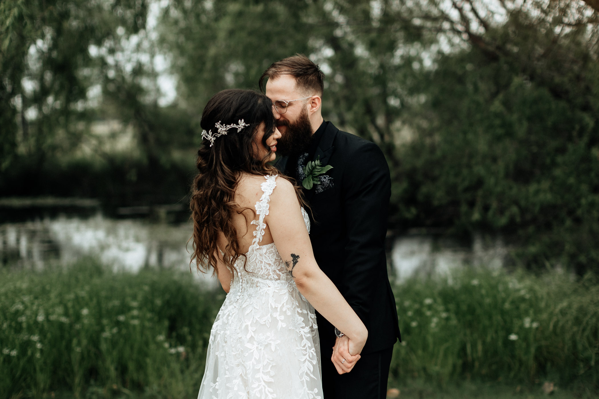 Bride and groom taking photos in front of a lake in DFW