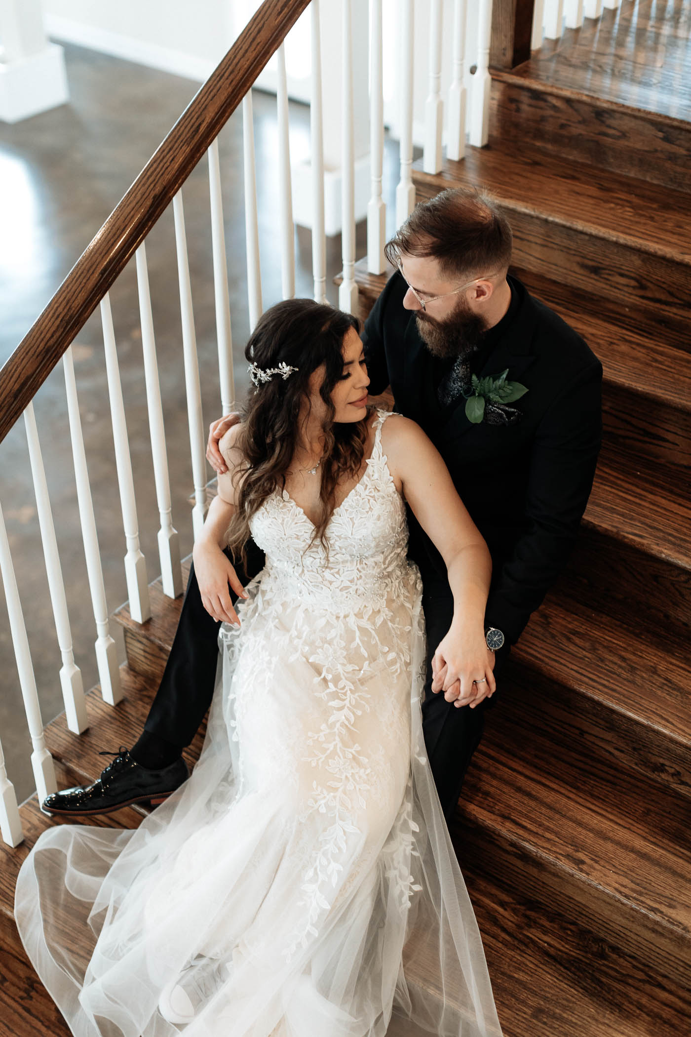 Bride and groom sitting down on stairs after wedding ceremony