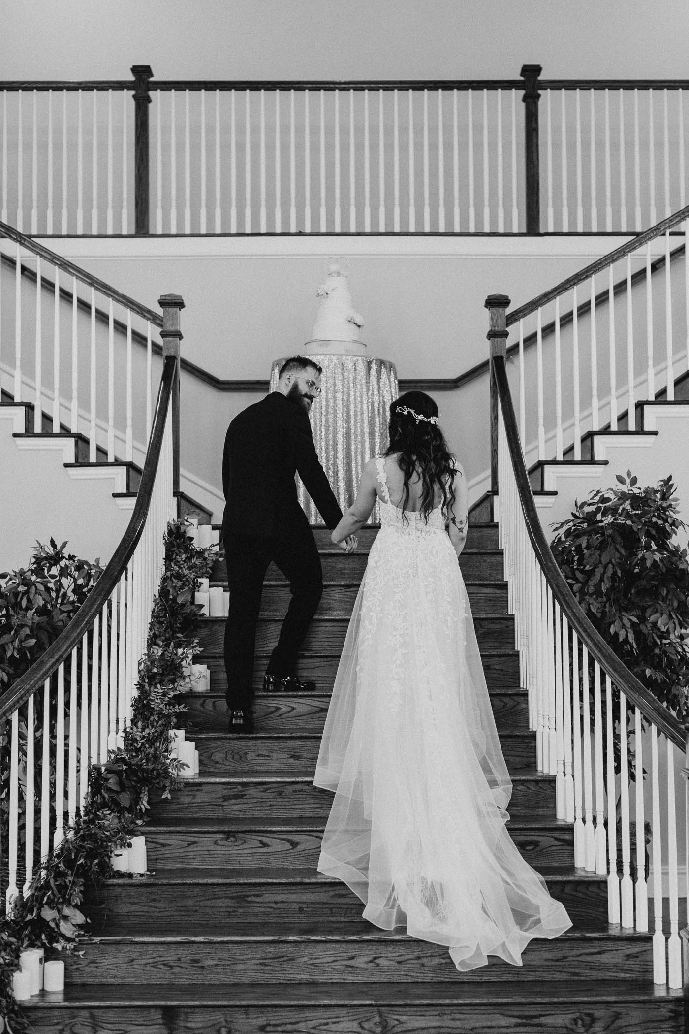 Black and white of bride and groom walking up stairs during wedding reception