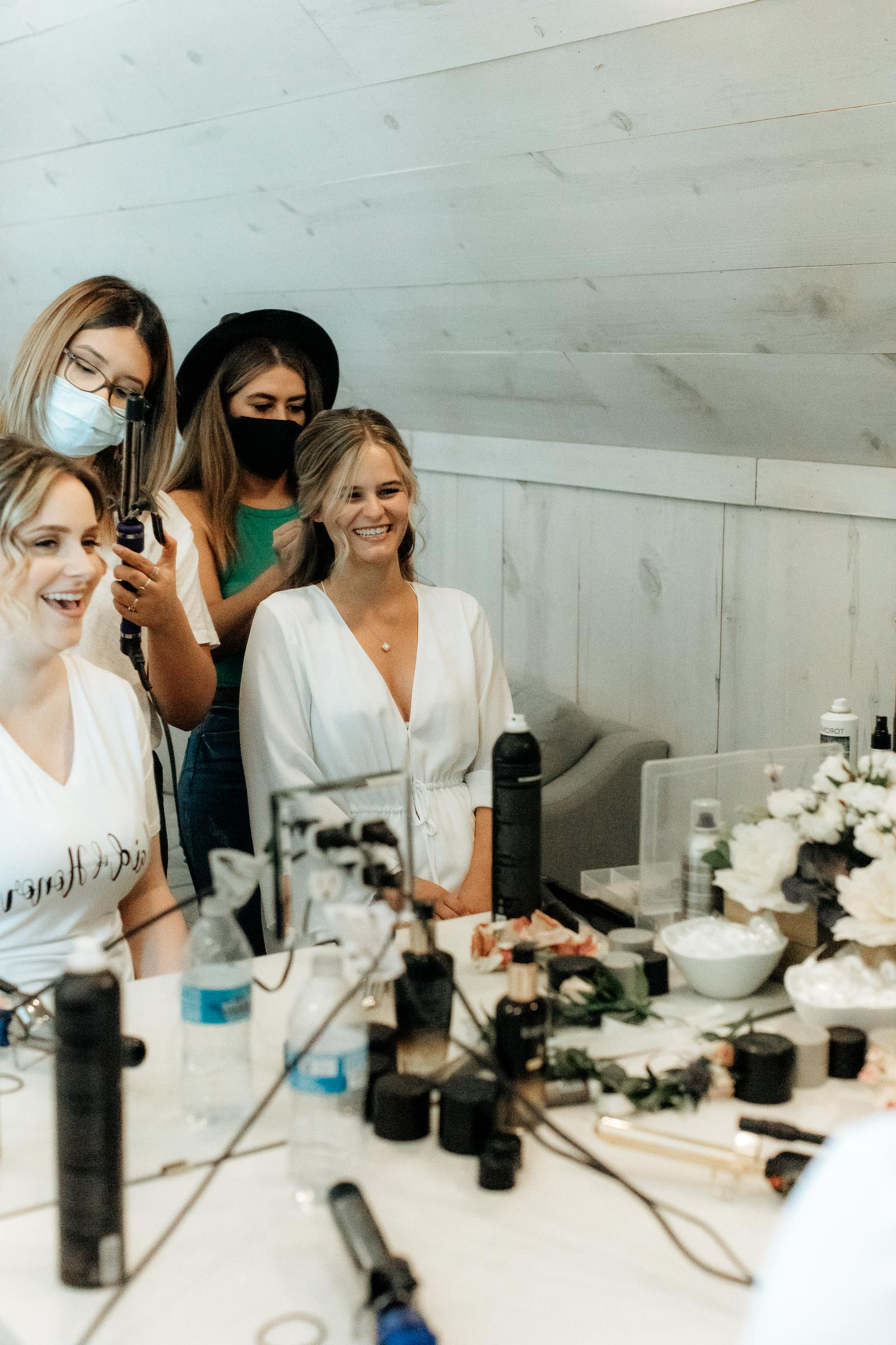 bride laughing with bridal party as they get ready for wedding day