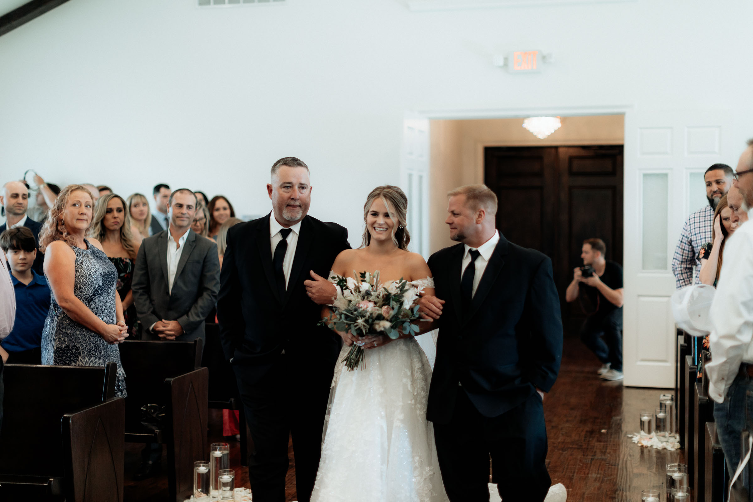 Bride walking down the aisle with her dad and step father
