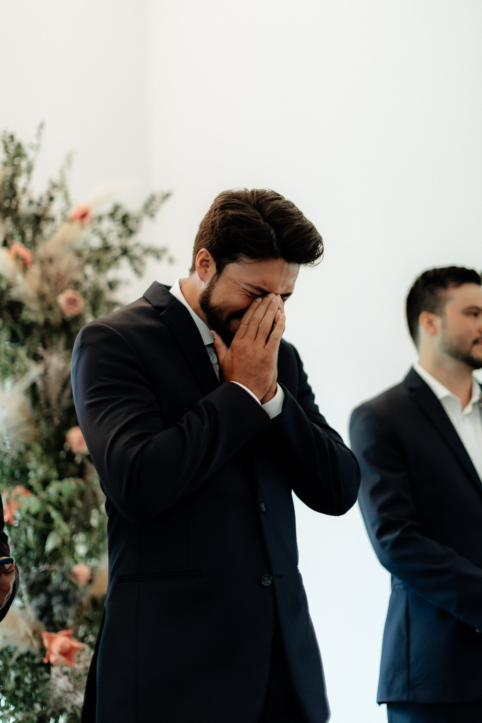 emotional groom holding back tears as he sees his bride for the first time on their wedding day