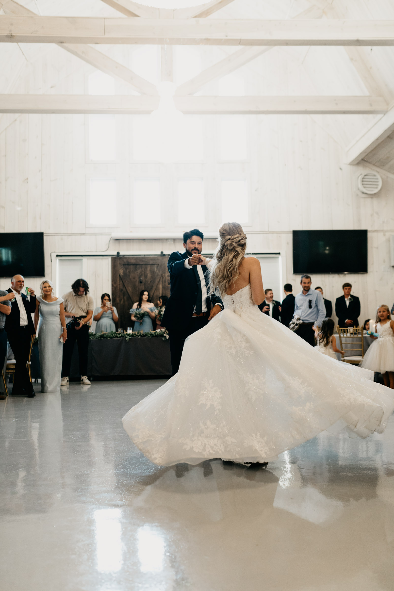 bride and groom sharing first dance and spinning around in white dress