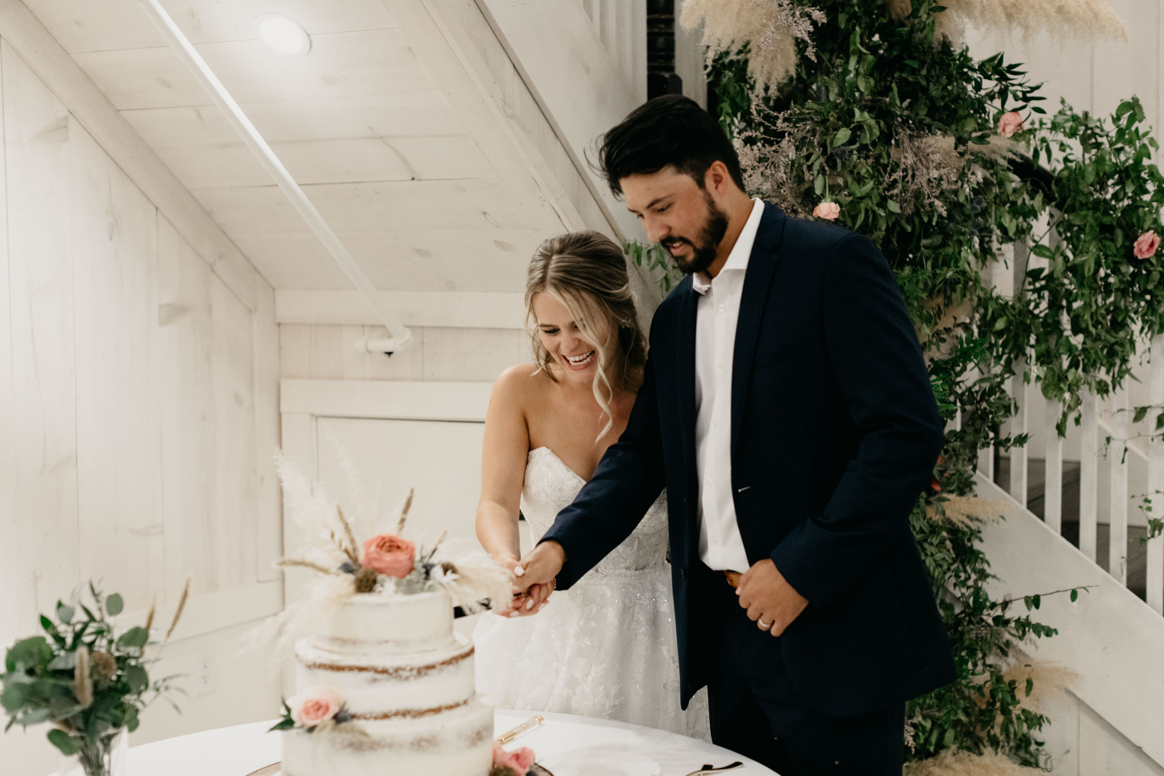 bride and groom cutting white wedding cake