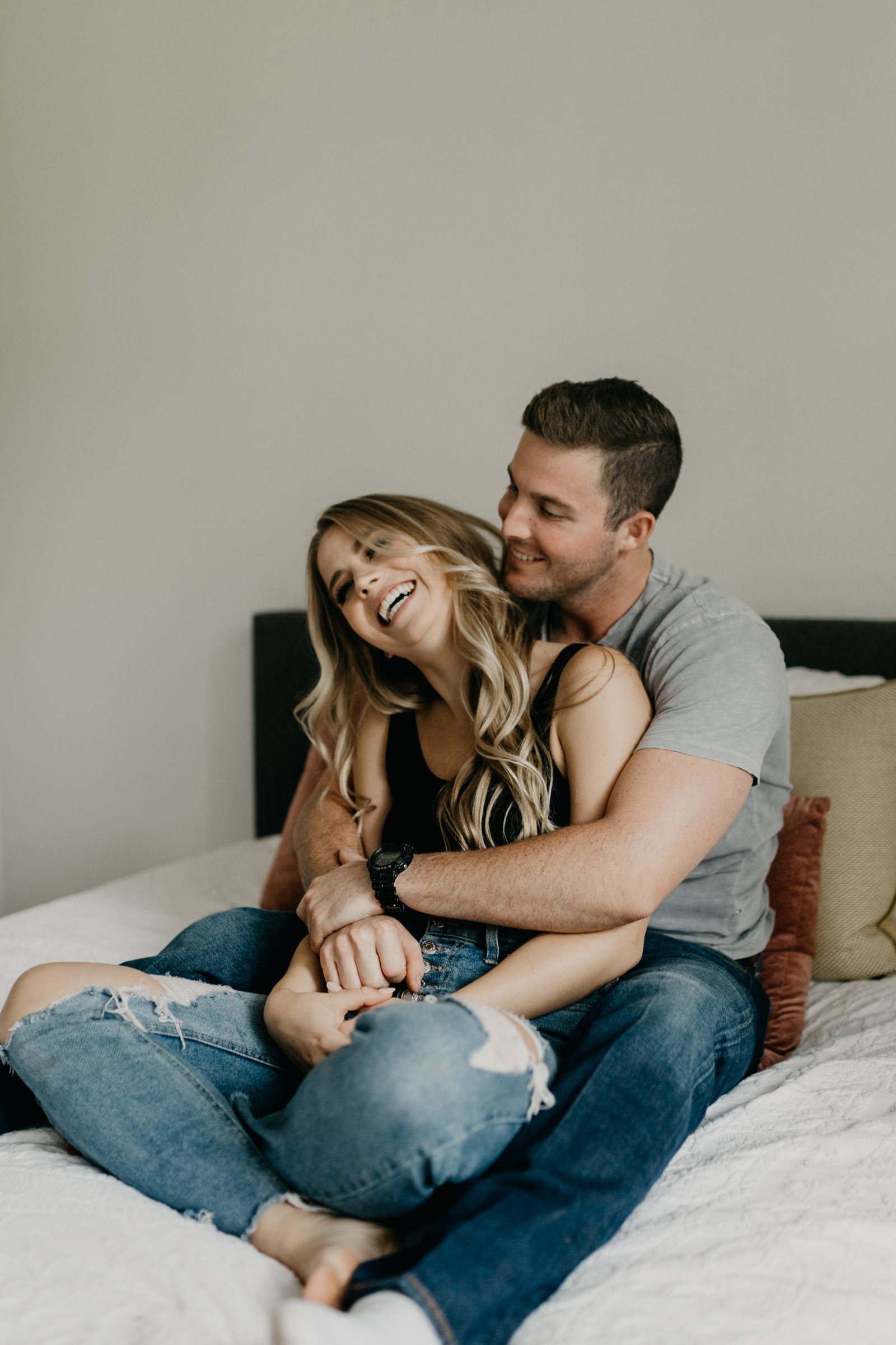 Playful photo of couple sitting on bed