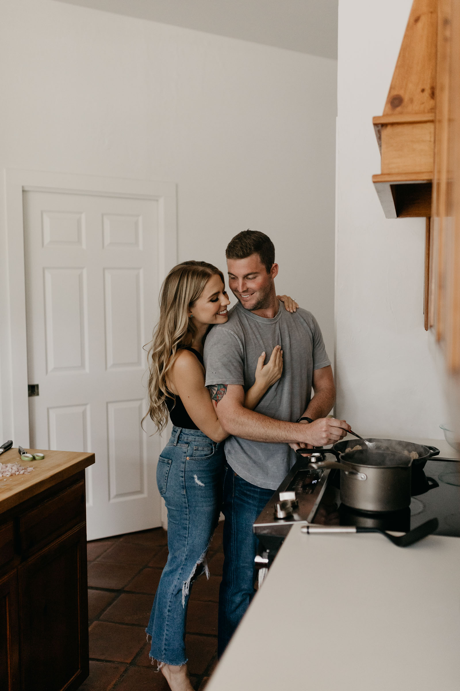 Engaged couple flirting while boy cooks dinner in boho kitchen