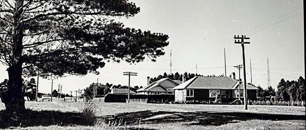 Original staff cottages built by Telefunken at Awarua Radio, seen in the early 1950s before additional housing was built at left of photo. Superintendent's and Faass residences visible. Receiving station in distance.