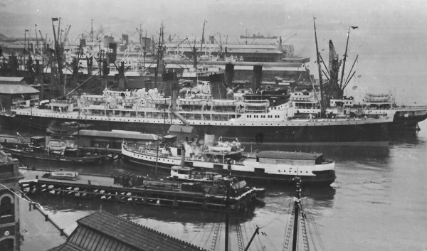 Wellington wharves in the 1940s. The 2-funnel vessel nearest the camera is TEV Rangatira with the Picton ferry Tamahine behind it and the Eastbourne harbour ferry nearer the camera. Two Federal Line vessels can be seen and I think the vessel between them would be either Rangitiki, or Rangitata of the New Zealand Shipping Company. The two masts at the bottom of the photograph belong to the scow Echo.