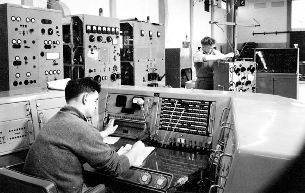 Ray Sutherland at the Himatangi Radio transmitter control console, Noel Bradbury standing in background