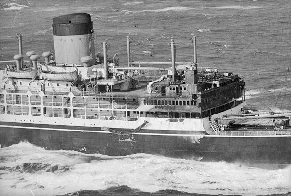 Fire damage to three decks, including the bridge, of the liner Gothic is clearly visible as she approaches New Zealand