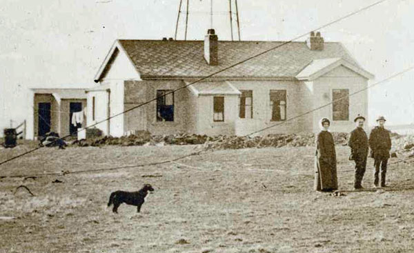 An enlarged view of the Chatham Islands wireless station building and onlookers during the raising of the second tower in 1913.