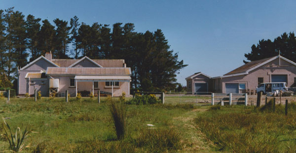 The original Awarua Radio buildings, seen in 1991, the year the station closed. At left, the original transmitter/receiver building (with double gables, behind the shed). At right, the engine house (later used as the transmitter building).
