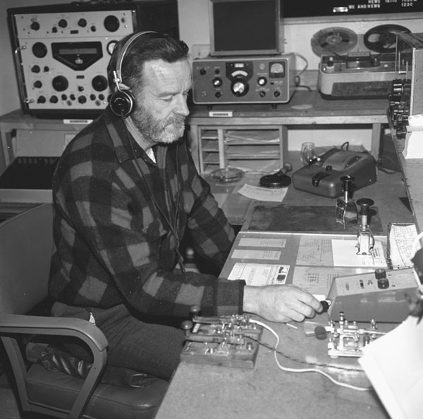 This photo taken during the 1972-1973 season at Scott Base shows the radio operator using a Heathkit HD-10 electronic keyer, although there is also a semiautomatic 'bug' key and two straight keys on the desk. In the background at the left is a Racal RA17 receiver with the RA63 single sideband adapter. In the centre of the shelf is a Collins 51S-1 receiver