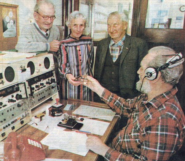 Mrs Margaret Dell shows Mr Terry Kelly, a radio operator at Awarua Radio, a glass insulator which formed part of the 400ft mast at the station until it was felled in 1938. Mrs Dell was at the station yesterday, along with Mr Nicholas Windle (left) and Mr George Jenkinson, as part of the preparations for the station's 75th jubilee in December.