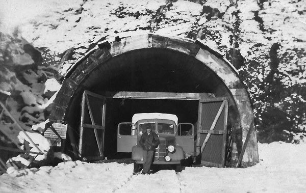 Western portal of the Homer Tunnel. The area around the truck was about the size of the pilot tunnel while the wider opening is the size of the finished tunnel.