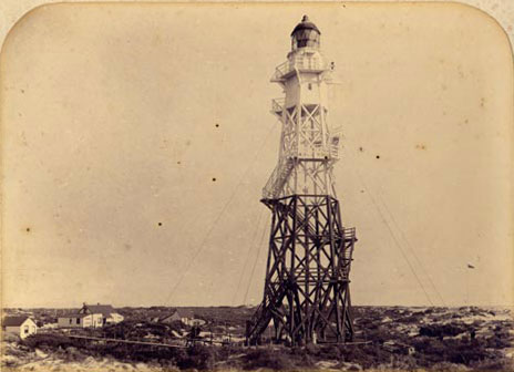 Commissioned in 1870, the first lighthouse at Farewell Spit was built cheaply and quickly of wood. The spit was not much above sea level, so the light needed to be on a high tower.