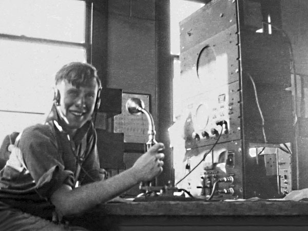 "Meteorologist LAC ""Dick"" Hay at the small ships desk, Awarua Radio, March 1946"