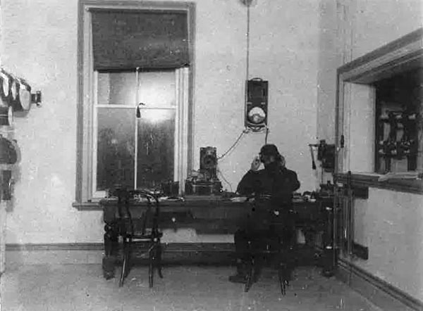 Operating desk at Awanui Radio c1913. Switchboard at left, window to high-tension room at right. The lever on the wall operates the aerial switch visible through the window.
