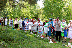 Worshippers standing opposite a spruce where men were conducting prayers in a sacred grove near the village of Marisola in the Marii El republic.