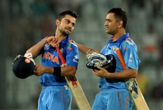 India captain Mahendra Singh Dhoni (R) greets batsman Virat Kohli (L)after India won the ICC World Twenty20 cricket tournament second semi-final match against South Africa at The Sher-e-Bangla National Cricket Stadium in Dhaka on April 4, 2014. India plays Sri Lanka in the final. AFP PHOTO/ PUNIT PARANJPE (Photo credit should read PUNIT PARANJPE/AFP/Getty Images)