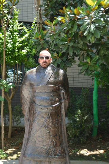 Chuck standing behind the metal statue of the costume of a Chinese warrior
