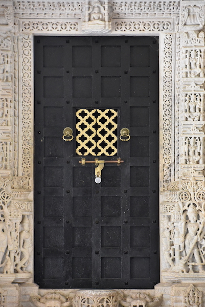 Wooden door surrounded by carved white marble