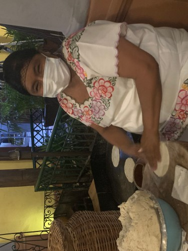 woman wearing a mask while making tortillas at La Chaya Maya in Merida Mexico