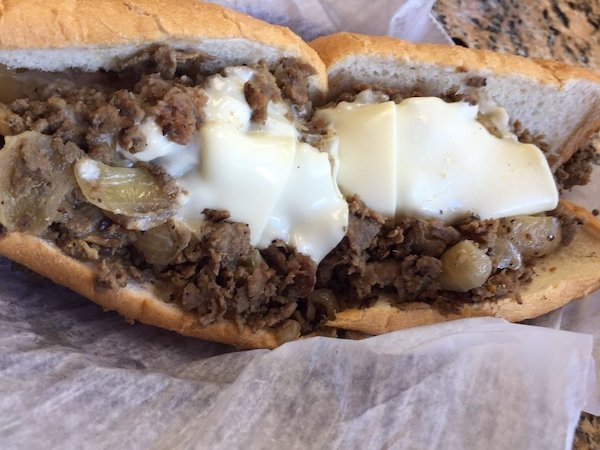 horrible Philadelphia Cheesesteak spread across two rolls with Cheese layer on top
