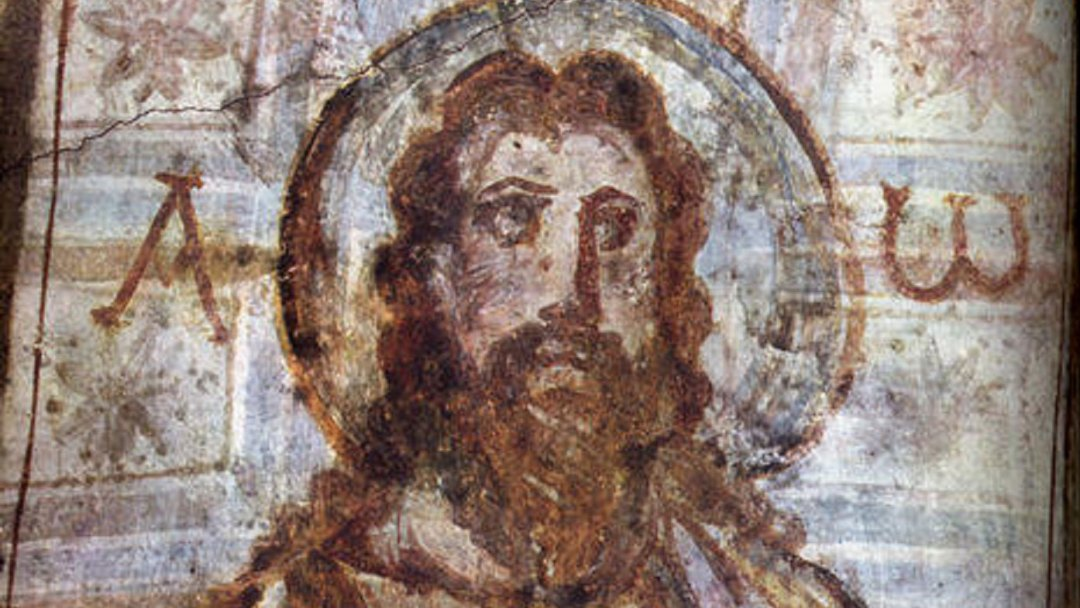 Portrait of Jesus Christ with beard, alpha and omega, depicted in a mural at the catacomb of Commodilla, late 4th century.