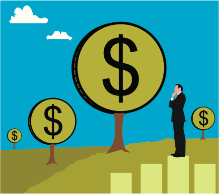 Businessman standing on a bar graph looking at a money tree
