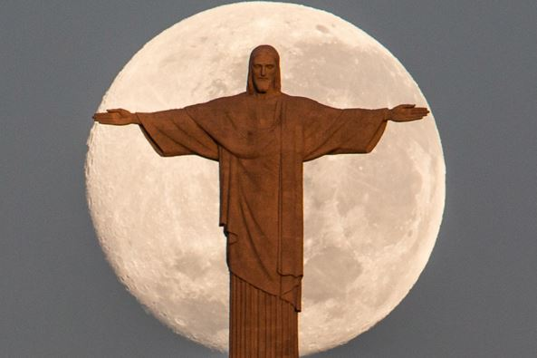 Moon behind statue of Christ in Rio