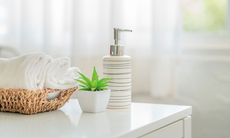 Clean bathroom with view of the corner of a counter, featuring a white ceramic shampoo bottle, fake plant and a basket of towels