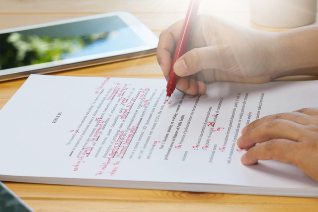person self-edits manuscript with red pen