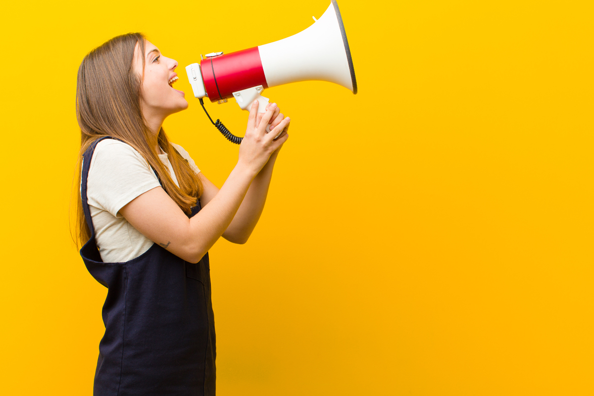 image of woman yelling on megaphone for crisis communication article header