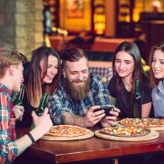 Young men and women gathering around looking at a cell phone - customer engagement marketing