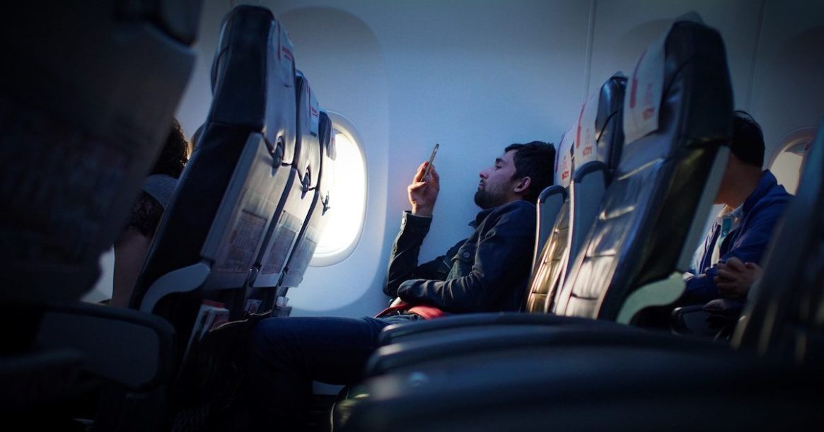 Man reading mobile phone on aircraft 1200x630pxl