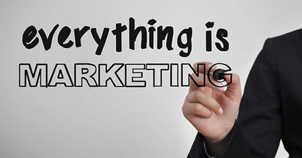 Mão escrevendo em inglês Everything is Marketing - para ilustrar que tudo é marketing, direcionando os conceitos marketing para quem não é do marketing.