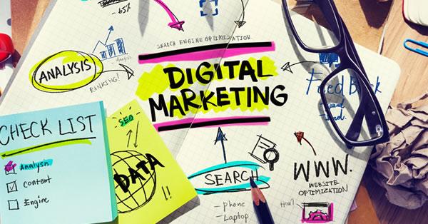 """Diversos itens de escritório em uma mesa com o termo """"Digital Marketing"""" escrito numa folha em destaque para ilustrar a evolução dos 4Ps."""