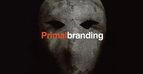 Primal Branding escrito sobre fundo preto, junto à uma máscara de tecido primitivo frequentemente utilizada para ilustrar o que é primal branding