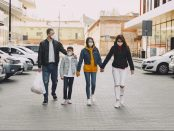 Family holding hands and walking together in the middle of a parking lot.