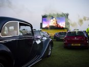 cars parked in front of an outdoor cinema screen