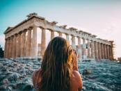 a woman taking a photo of Greek architecture