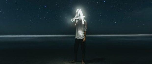a faceless figure standing on a beach